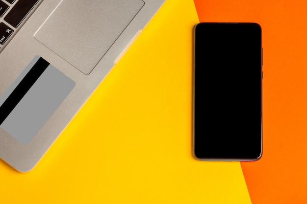 Ordinateur portable, smartphone avec écran noir et carte de crédit, vue de dessus