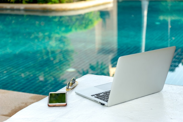 Ordinateur portable et smartphone près de la piscine, l'homme d'affaires moderne peut travailler n'importe où.