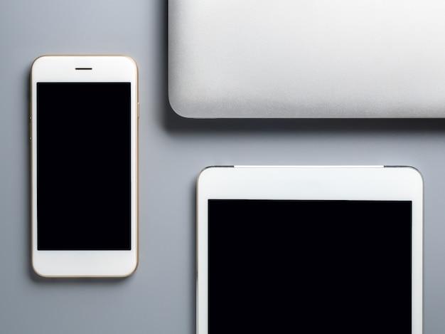 Ordinateur portable, smartphone et tablette sur fond gris