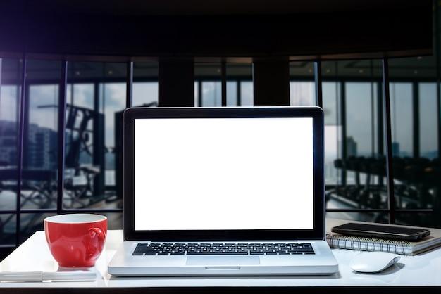 Ordinateur portable, smartphone et tablette vue de face sur le bureau au bureau et en arrière-plan