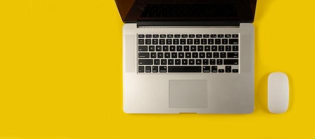 Ordinateur portable et souris isolé sur jaune