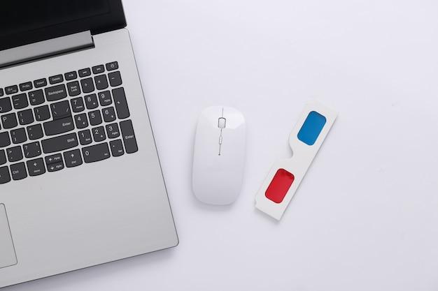 Ordinateur portable, souris pc et lunettes 3d anaglyphes sur fond blanc. vue de dessus. minimalisme