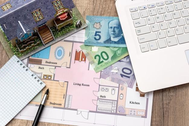 Ordinateur portable avec stylo et calculatrice en dollars australiens de plan de maison