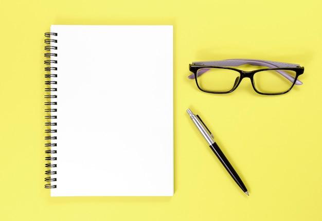 Ordinateur portable, stylo et lunettes sur fond jaune pour maquette