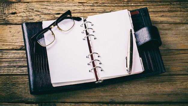 Ordinateur portable avec stylo et lunettes. image tonifiée.