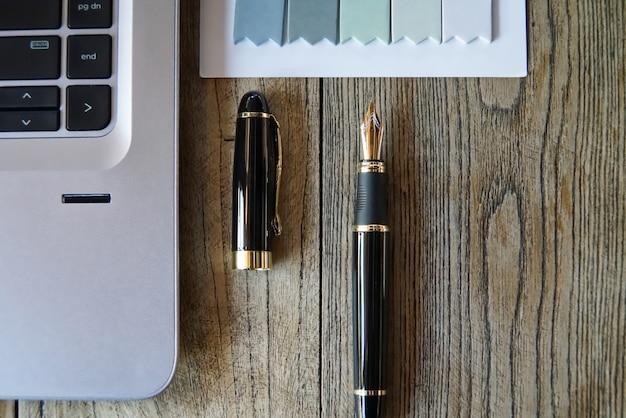 Ordinateur portable et stylo de luxe sur une table de travail