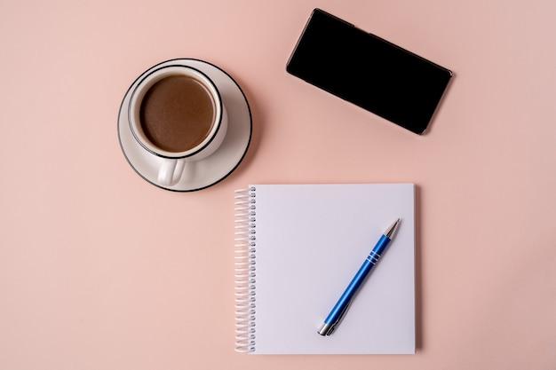Ordinateur portable avec un stylo, un smartphone et une tasse de café.