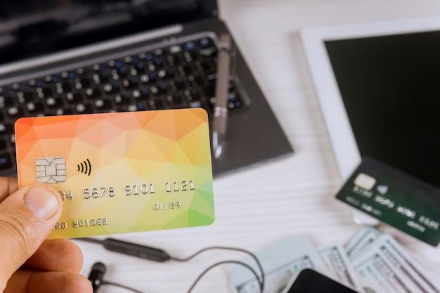 Ordinateur portable avec stylo, tablet pc avec argent et carte de crédit, téléphone, sur fond en bois
