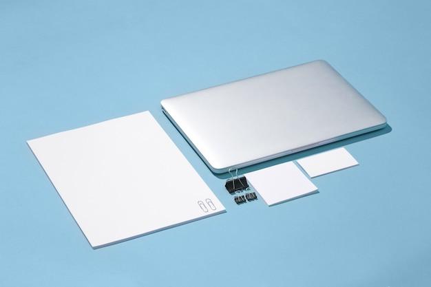 L'ordinateur portable, stylos, téléphone, note avec écran blanc sur table