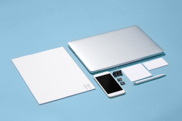L'ordinateur portable, stylos, téléphone, note avec écran vide sur table