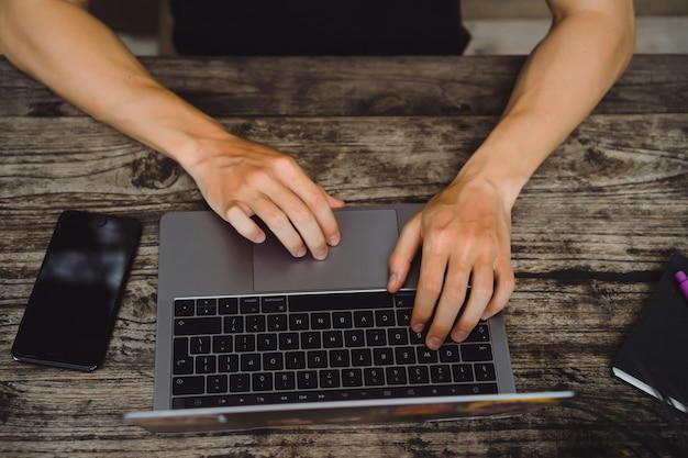 Ordinateur portable sur une table en bois, les mains d'un homme travaillant sur un ordinateur