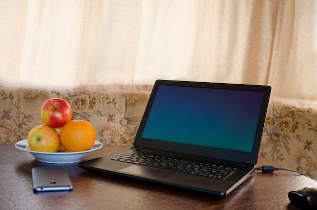 Ordinateur portable sur une table dans une cuisine confortable avec une assiette de fruits, un smartphone. pause
