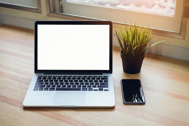 Ordinateur portable sur la table dans le fond de la salle de bureau, pour le montage de l'affichage graphique.