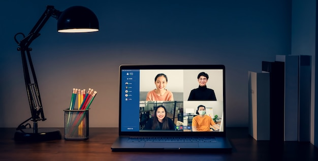 Ordinateur portable sur table dans la nuit avec une réunion par appel vidéo pour faire équipe en ligne et présenter des projets de travail. concept travaillant à domicile.