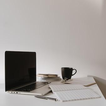 Ordinateur portable sur table avec tasse à café, feuille de papier contre mur blanc