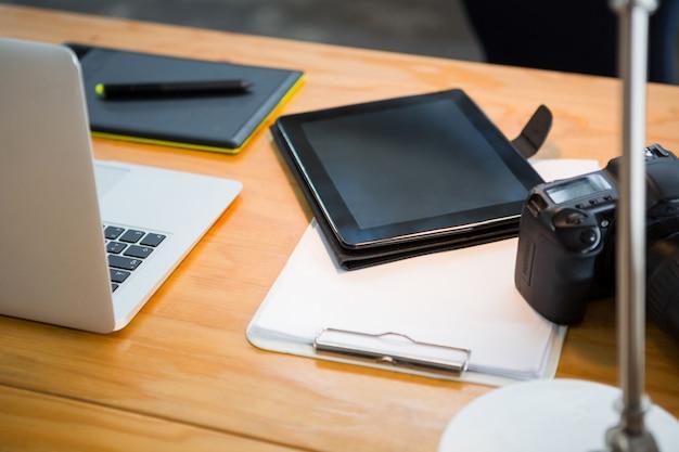 Ordinateur portable, tablette numérique et appareil photo numérique sur le bureau