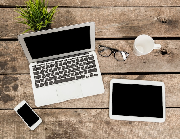 Ordinateur portable, tablette numérique et smartphone avec écran de copie sur la vue de dessus de table en bois