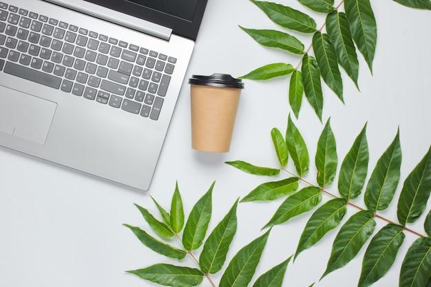 Ordinateur portable, tasse à café sur fond blanc avec des feuilles vertes. concept d'unité avec la nature. eco nature morte. vue de dessus