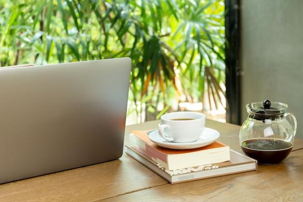 Ordinateur portable et tasse de café avec livre sur une table en bois à café.