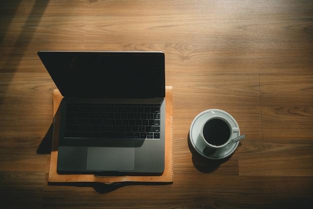 Ordinateur portable et tasse à café sur plancher en bois