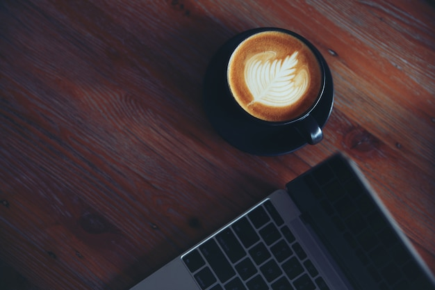 Ordinateur portable avec une tasse de café sur la table en bois au café café.