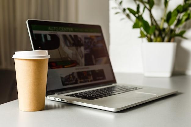 Ordinateur portable avec une tasse de café sur une table.