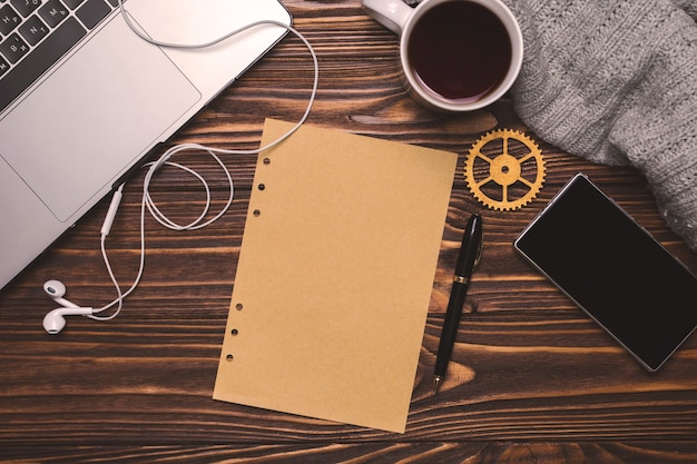 Ordinateur portable, tasse avec thé ou café, écouteurs, téléphone, écharpe tricotée grise, équipement doré, stylo et papier