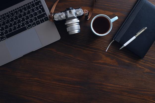 Un ordinateur portable, une tasse de thé, une caméra et un cahier sont allongés sur une table en bois sombre. le lieu de travail d'un photographe ou d'un pigiste. fond
