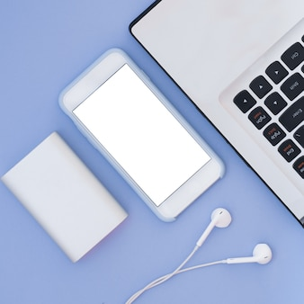 Ordinateur portable, téléphone, casque et banque d'alimentation sur fond bleu. composition à plat et place pour le texte. vue de dessus.