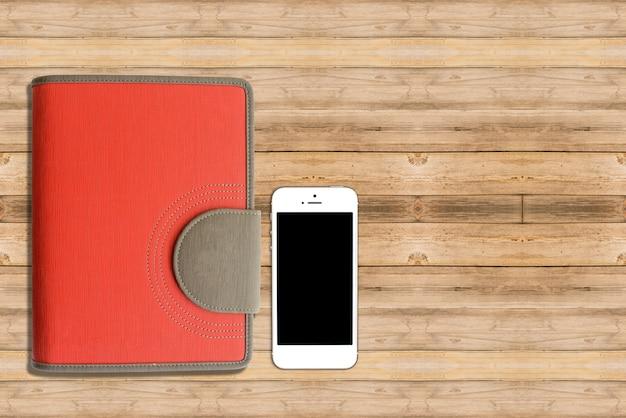 Ordinateur portable avec téléphone intelligent sur table de bureau en bois.