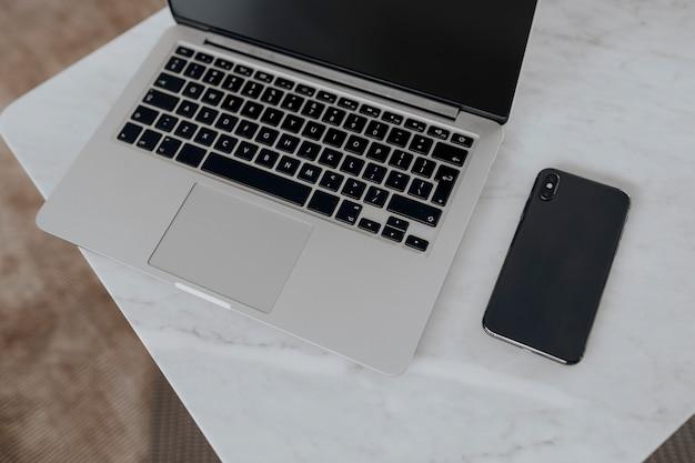 Ordinateur portable et un téléphone sur une table en marbre