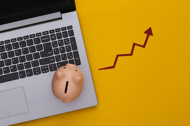 Ordinateur portable, tirelire avec flèche de croissance rouge sur jaune. graphique de flèche qui monte