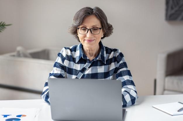Ordinateur portable de travail de femme âgée. femme d'affaires occupée à travailler sur un ordinateur portable au bureau à domicile