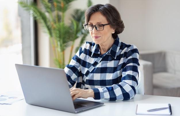 Ordinateur portable de travail de femme âgée sérieuse. femme d'affaires occupée à travailler sur un ordinateur portable au bureau à domicile