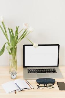 Ordinateur portable avec des tulipes dans un vase sur une table en bois
