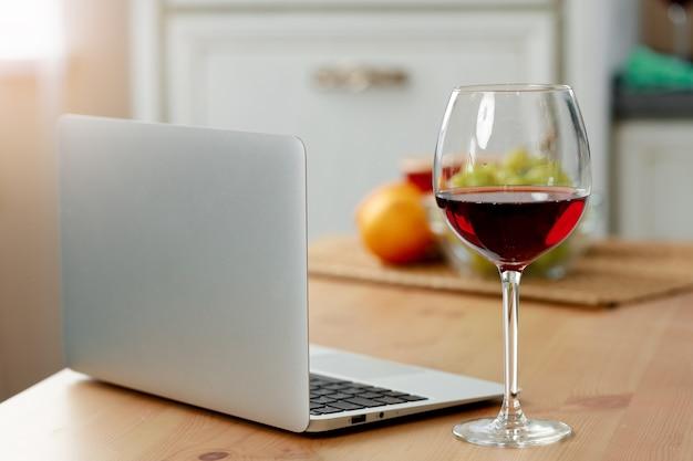 Ordinateur portable et verre de vin rouge sur la table de cuisine en bois se bouchent