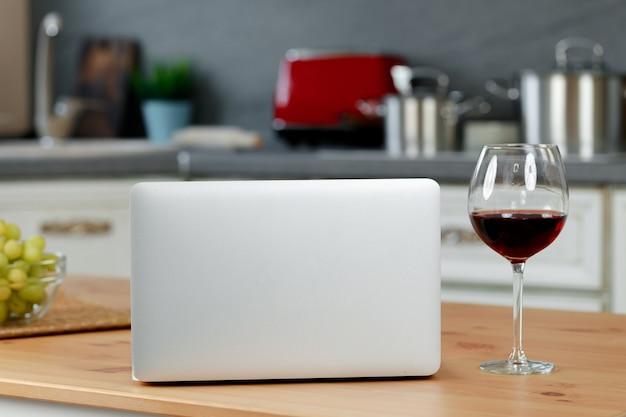 Ordinateur portable et verre de vin rouge sur la table de cuisine en bois