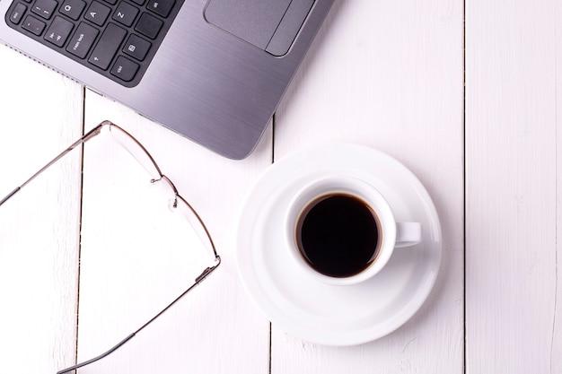 Ordinateur portable, verres et une tasse de café sur une table en bois blanche