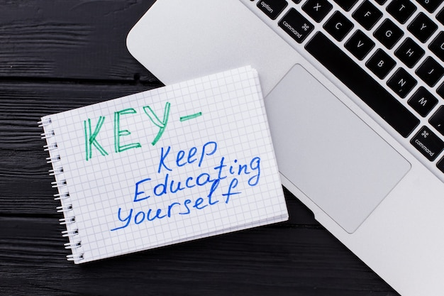 Ordinateur portable vue de dessus et bloc-notes avec abréviation. clé - continuez à vous éduquer. fond en bois sombre.