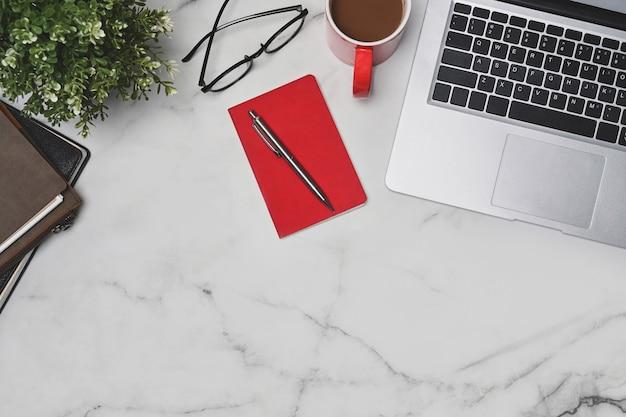 Ordinateur portable vue de dessus, ordinateur portable, tasse à café et verres sur table en marbre.