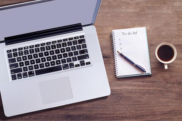 Ordinateur portable vue de dessus avec le texte de la liste des tâches sur la note du livre avec une tasse de café, un stylo et un smartphone.