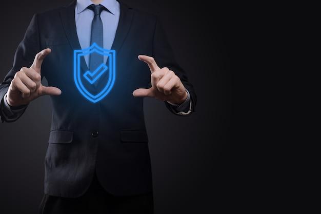 Ordinateur de sécurité du réseau de protection entre les mains d'un homme d'affaires. concept d'entreprise, technologie, cybersécurité et internet - homme d'affaires en appuyant sur le bouton de bouclier sur les écrans virtuels protection des données.
