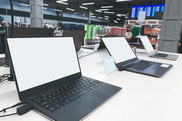 Des ordinateurs portables avec un écran blanc à la vitrine du magasin d'électronique.