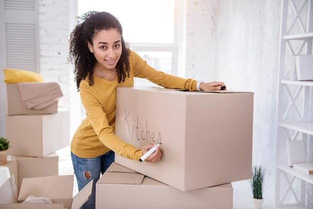 Ordre d'amour. charmante fille aux cheveux bouclés posant pour la caméra et souriant tout en signant une boîte avec des couverts de cuisine