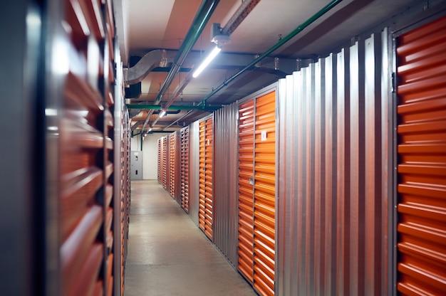 Ordre. une rangée uniforme de conteneurs de stockage sécurisés modernes et fermés dans une zone de stockage lumineuse et soignée