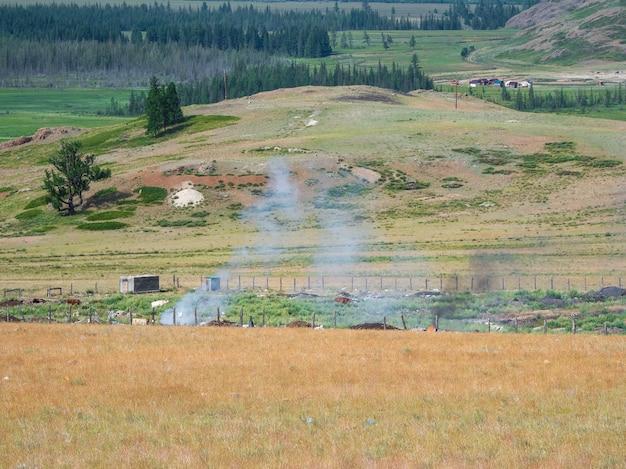 Les ordures brûlent sur le terrain. inferno d'incendie d'ordures de décharge dans la steppe de montagne avec une épaisse fumée.