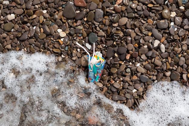 Ordures ménagères en plastique en mer. microplastique dans l'eau. gobelet jetable, fragments d'emballage et pailles à cocktail dans les vagues sur la plage.