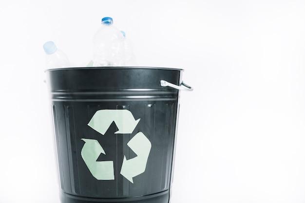 Ordures en plastique dans le seau de recyclage sur fond blanc