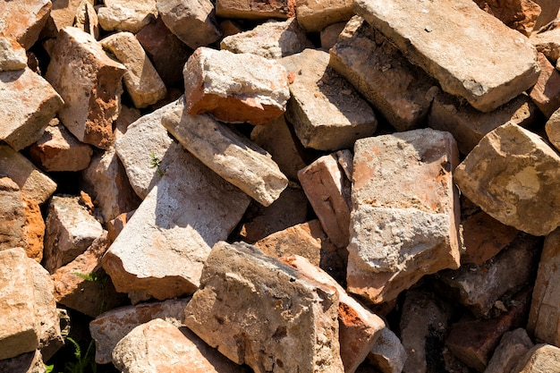 Des ordures et un tas de briques rouges près des ruines d'un ancien château ou forteresse, un bâtiment abandonné