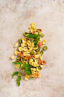 Orecchiette crue au parmesan et tomates, basilic à l'ail et huile sur une surface légère avec du poivre sur une surface brun clair